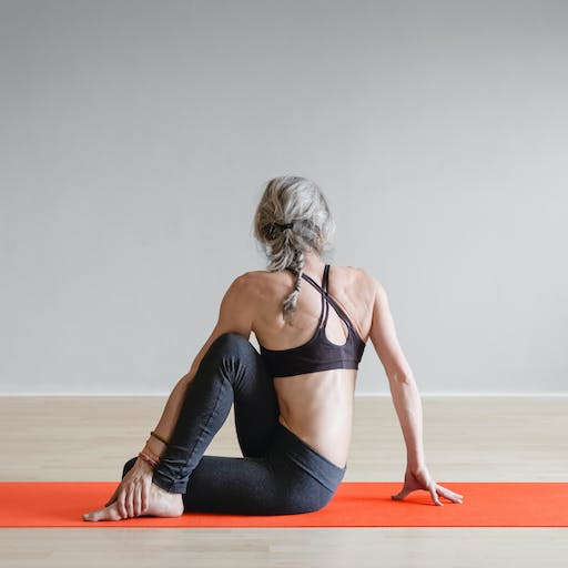 A person practicing yoga on an orange yoga mat