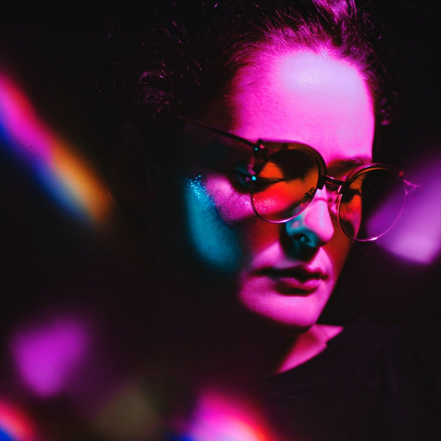 A woman wearing glasses, illuminated with a pink light.