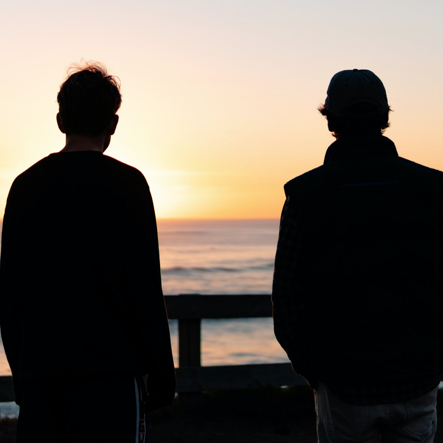 Two people's silhouettes, staring out at the sunset over an ocean.