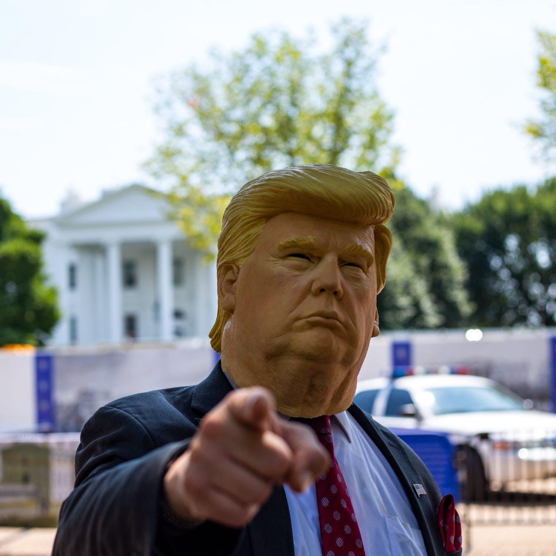 A man wears a Donald Trump mask
