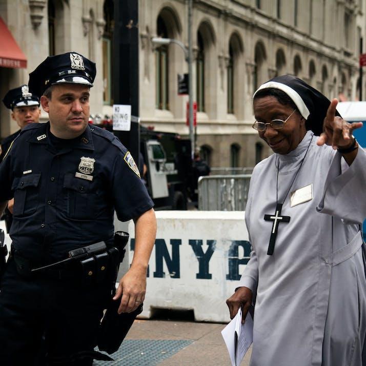 A black nun talks to a white police officer