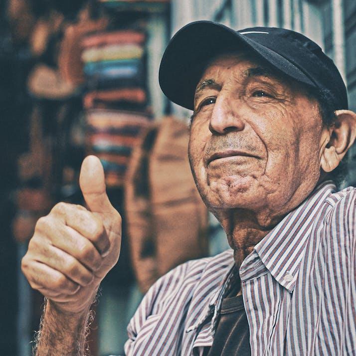 An older man wearing a baseball cap gives a thumbs up.