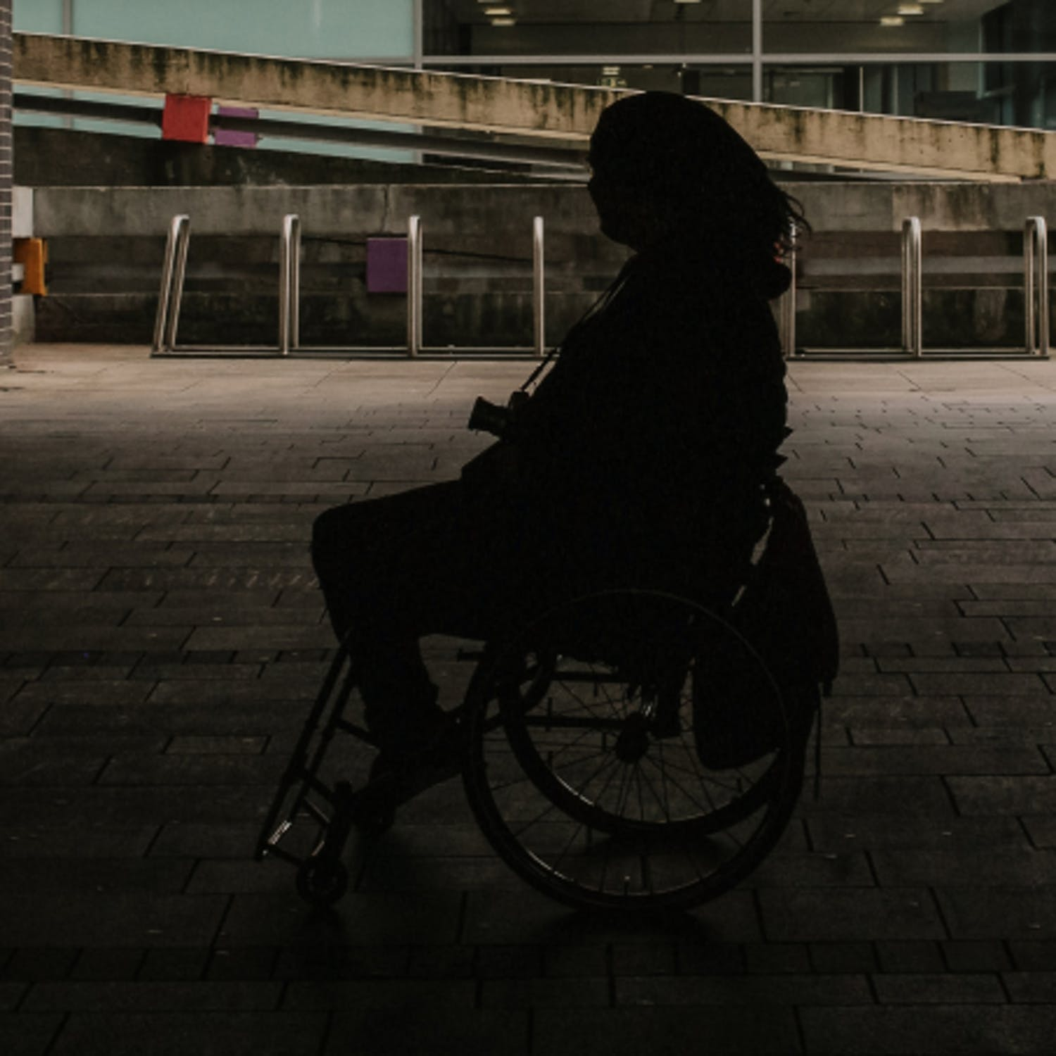 Silhouette of woman in wheelchair outside.