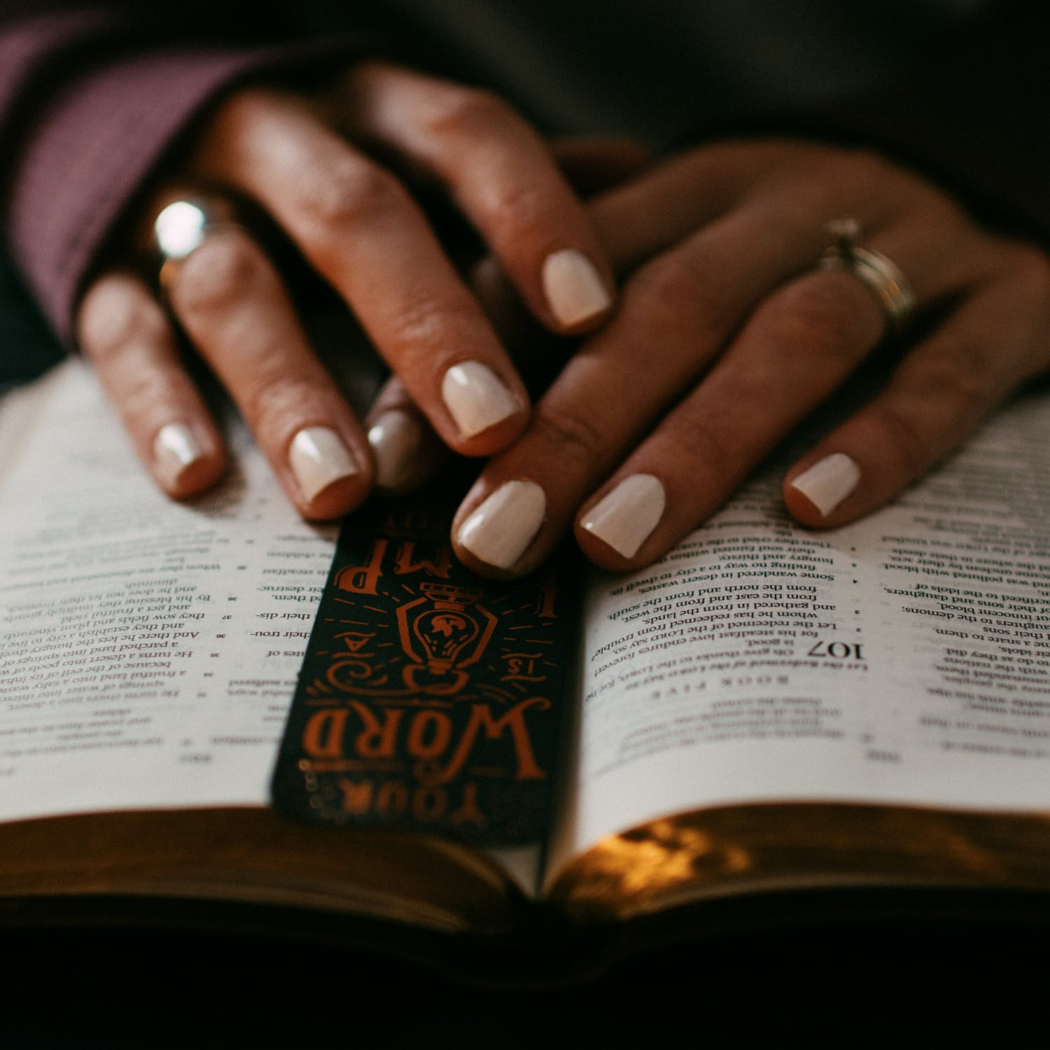 Two hands over a Bible.