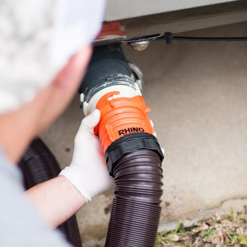 A man pumping sewage from an RV