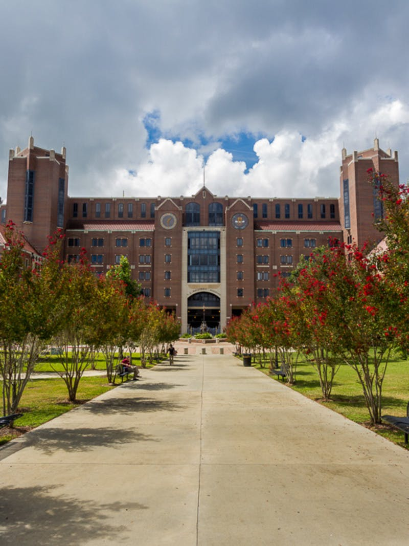 Tree-lined walkway to Doak S. Campbell Stadium brick building at Florida State University in Tallahassee, Florida.