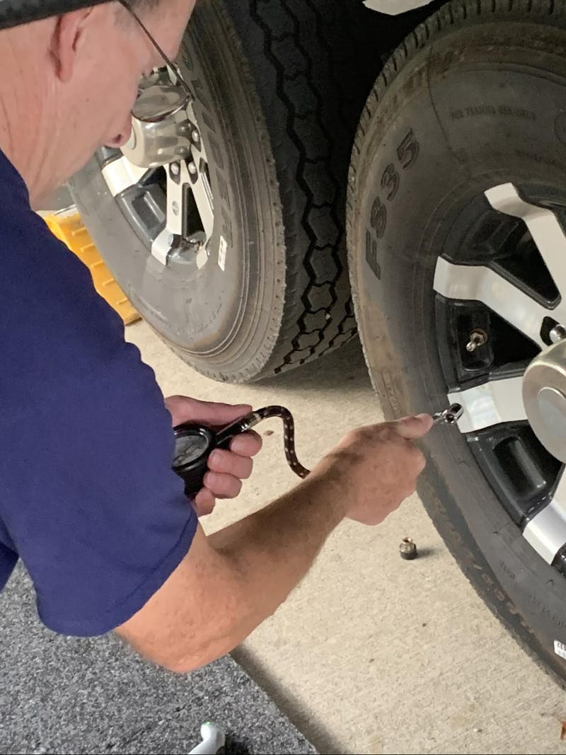 Tom Boswell showing how to check tire pressure on his RV.