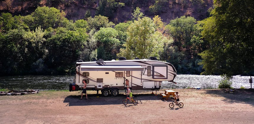 Young boys play and ride bikes in front of an RV near a river.
