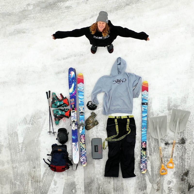 Ryan standing in an overhead shot of his ski gear laid out on the ground.