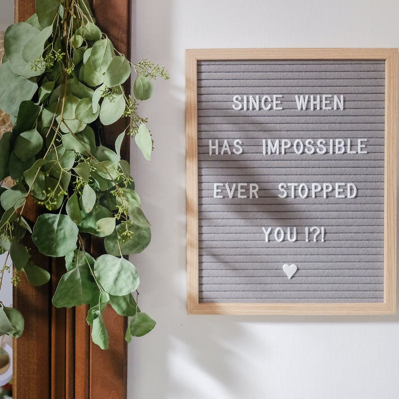 "A sign reading ""Since when has impossible ever stopped you?"""