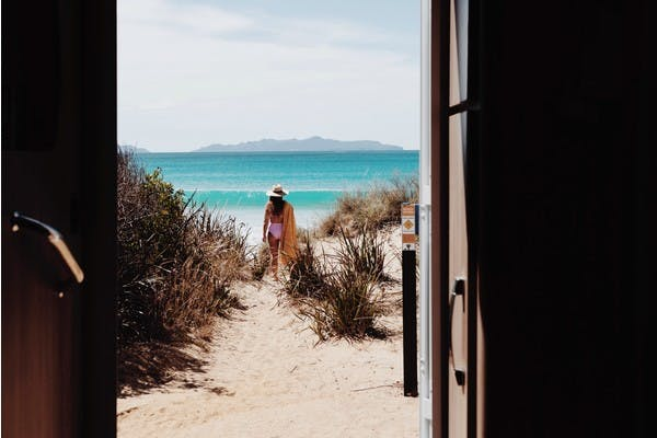 A view from the inside of an RV looking out the doorway to Kelvedon Beach, in Tasmania, Australia. With Sarah Glover in the background looking out to the ocean.