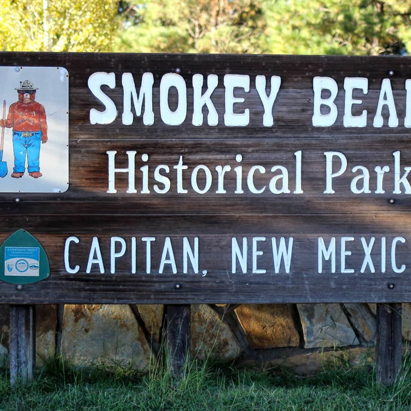 Dark wooden sign for Smokey Bear Historical Park in Capitan, New Mexico