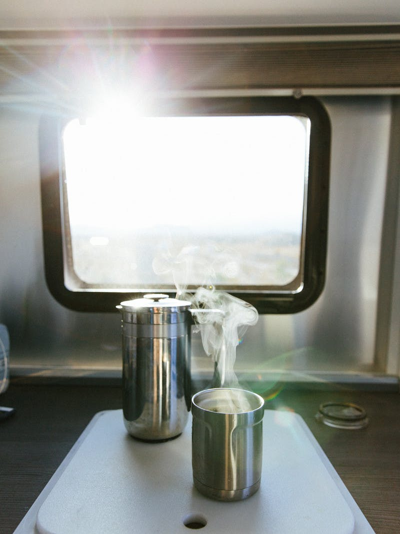 Steaming cup of coffee, next to a metal French press, in front of an RV window.