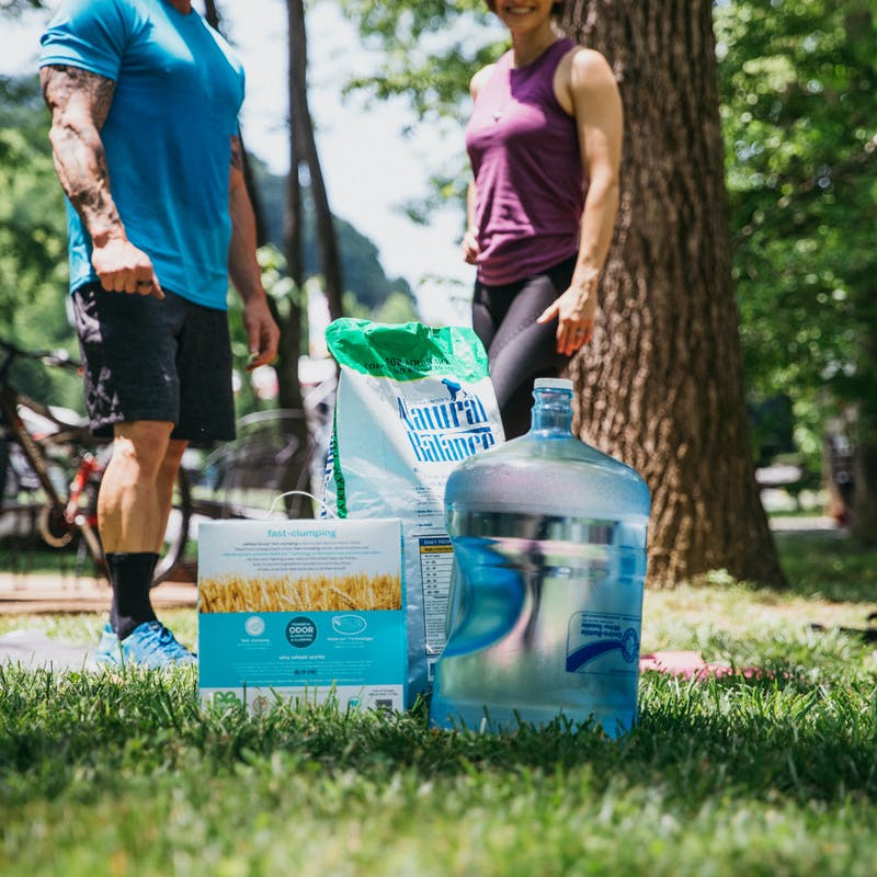 A 5-gallon water jug, a box of cat litter and a bag of dog food sitting in the grass, demonstrating what home items you can use as weights during a workout.
