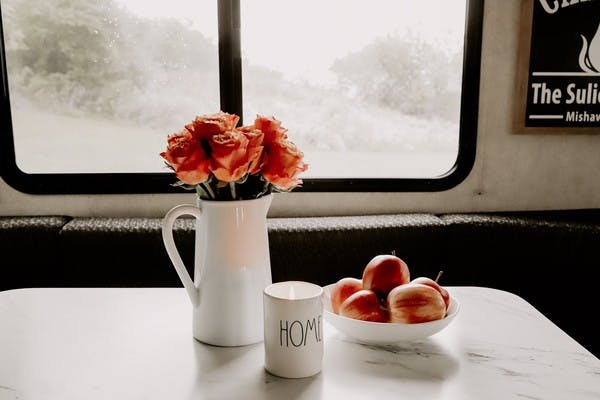 "A vase of roses, a bowl of crisp apples and a glowing candle that reads ""Home"" sit on an RV table in front of a foggy window to the outdoors."