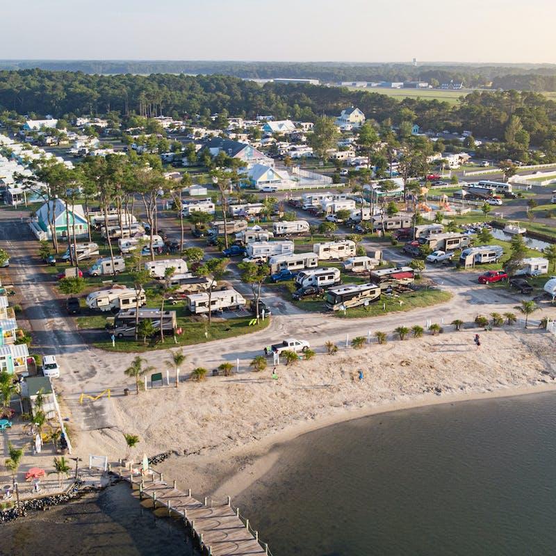An aerial shot of an RV park near the beach.