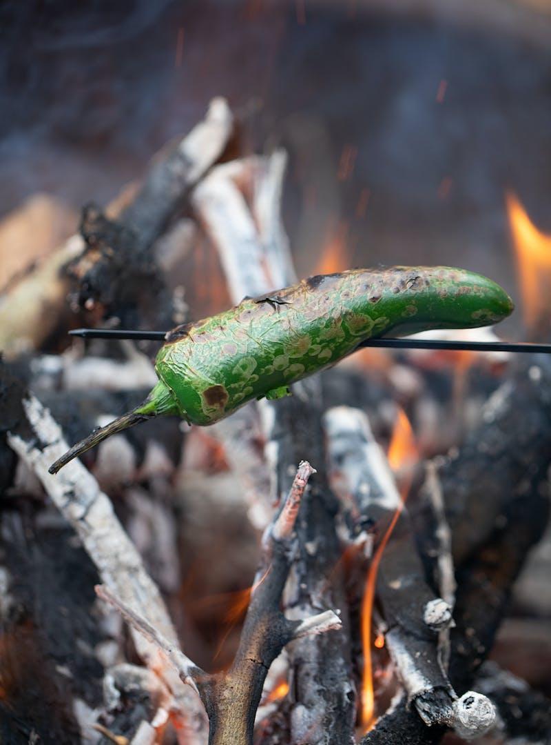 A jalapeño roasting over an open flame.