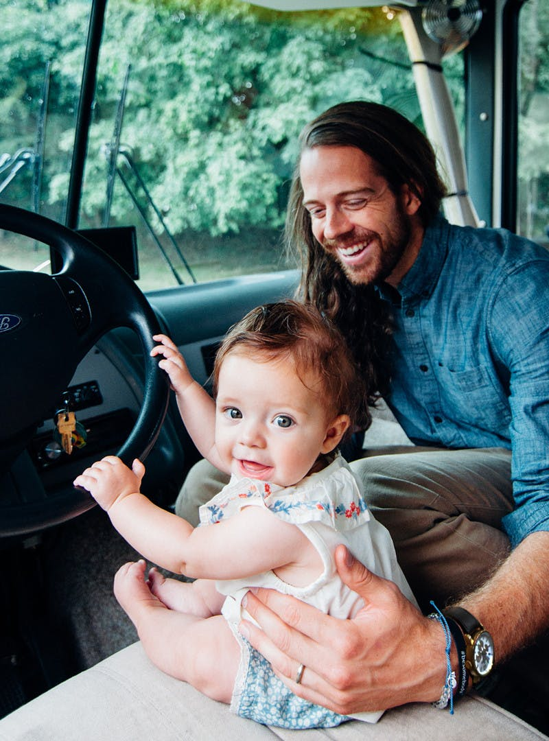 Bryce and Avalyn Jurgy inside the motorhome, baby trying to steer RV in driver's seat, while man holds and smiles from passenger seat.
