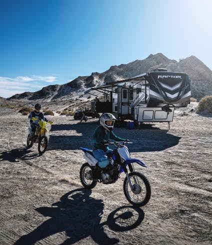 Two people ride dirt bikes in front of a toy hauler rv.