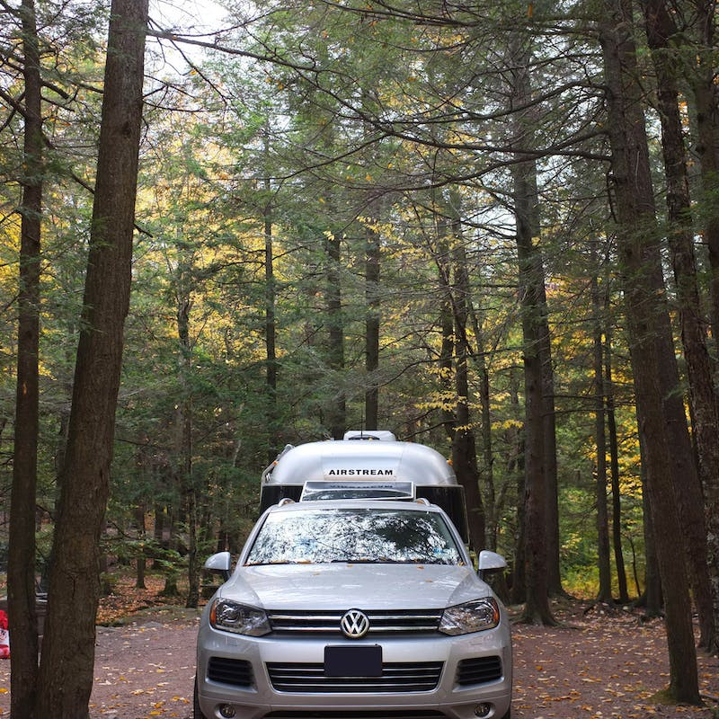 Dr. Na's Airstream and car parked in a wooded campsite.