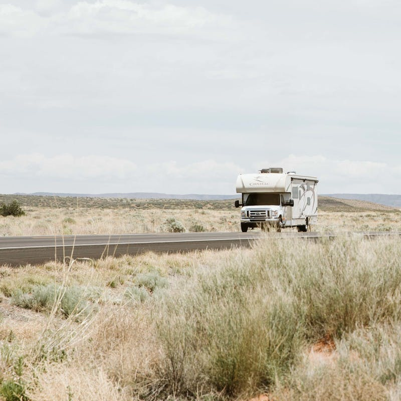 Class C motorhome drives along road, surrounding by plains with tall brown grass.