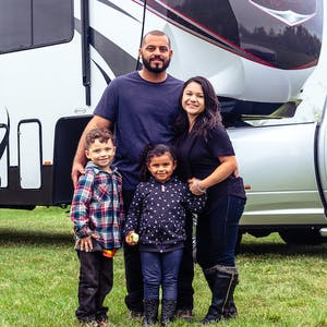 The Class Family posed outside with their toy hauler RV.