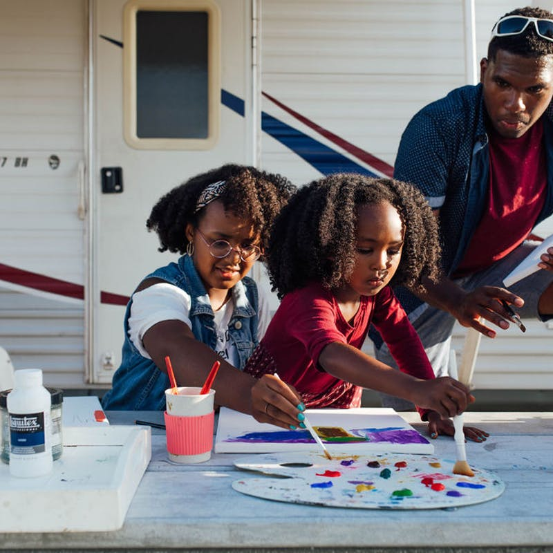 A dad and his two daughters painting at a picnic table outside an RV.