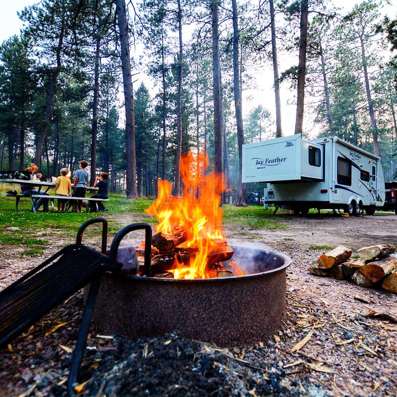 A roaring fire in a pit at an RV campground.