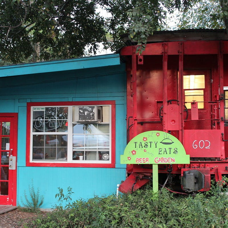 The Crum Box Gastgarden restaurant, a blue building with red train caboose and green beer garden sign, in Railroad Square Art Park in Tallahassee, Florida.