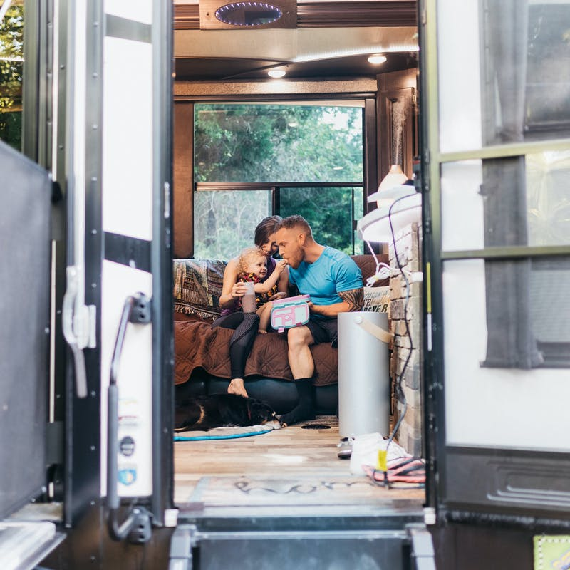 A young family eating snacks together on a couch inside an RV.