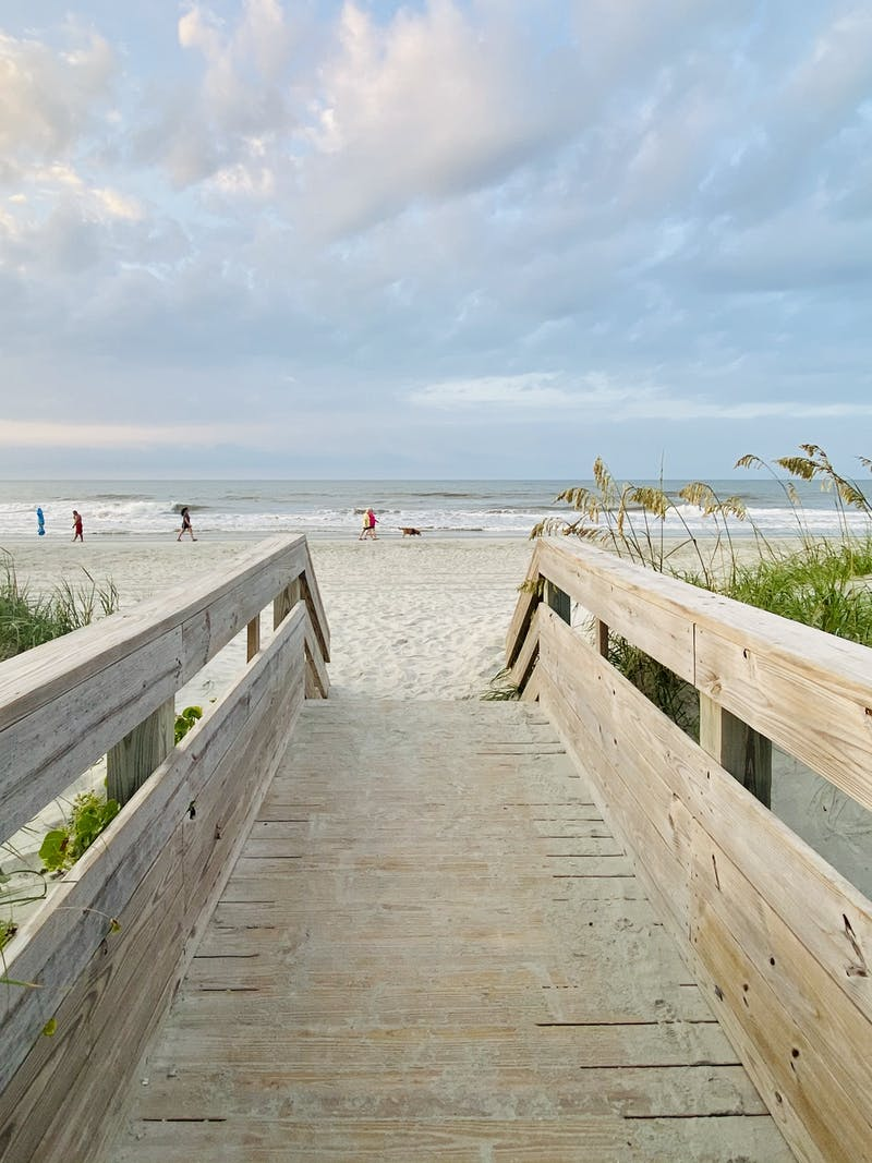A photo of a boardwalk opening up to the beach.