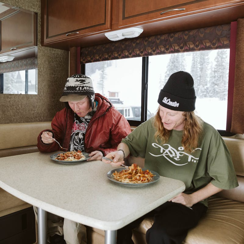 Two young guys in a Class A motorhome sit and eat spaghetti