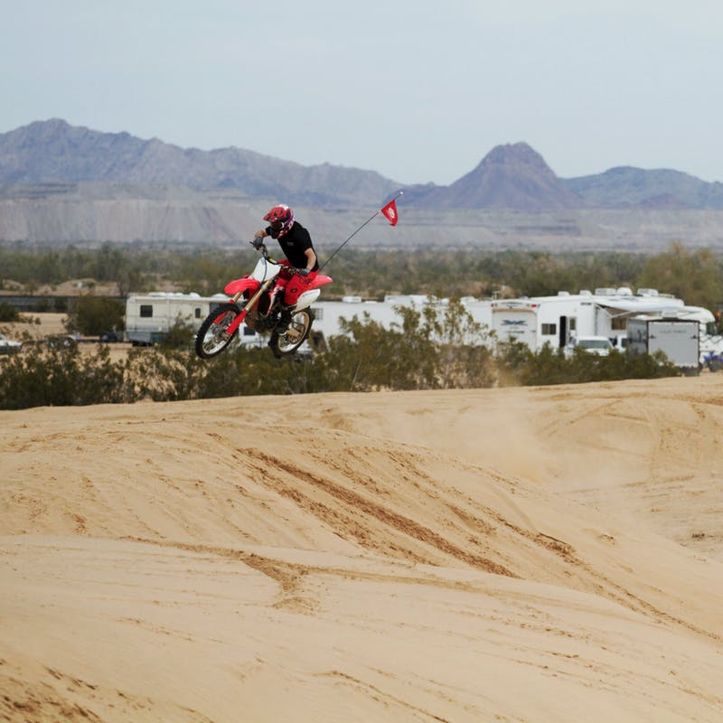 A dirt biker getting air over a sandy dune with RVs in  the distance.
