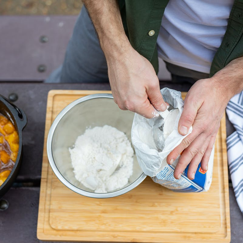 Measuring out flour into a bowl for the cobbler topping.