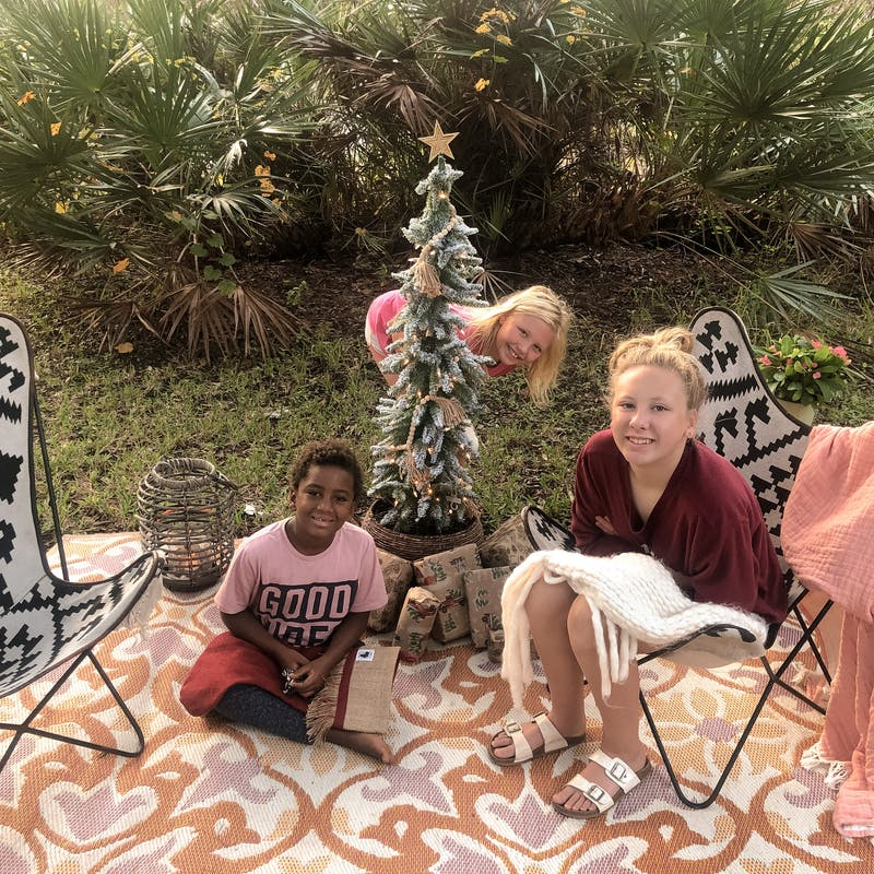 Shannon Carew's children sit outside next to a Christmas tree at their campsite.
