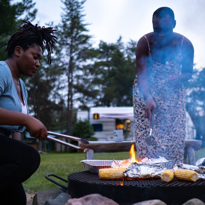 Chanel and Brittany Tate cooking over an open fire with a Jayco Travel Trailer RV in the background.