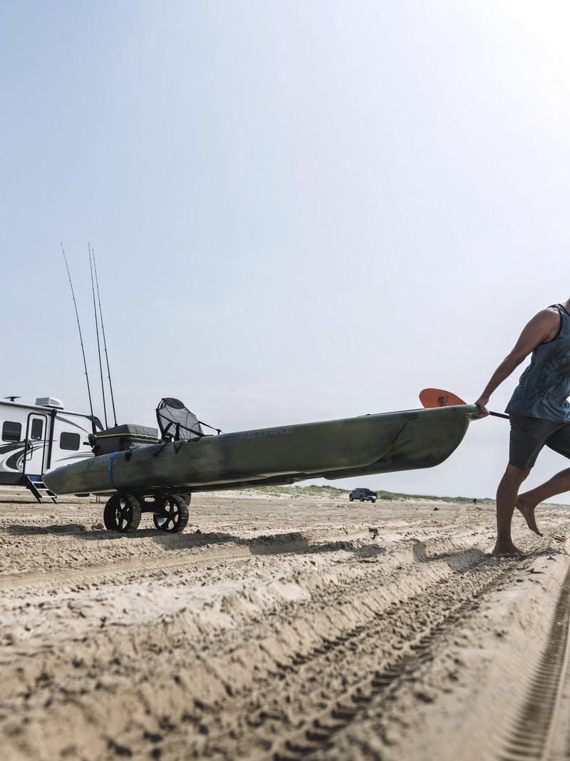 Robert Fields pulls his kayak across a sandy beach that he's unloaded from this Cougar travel trailer.