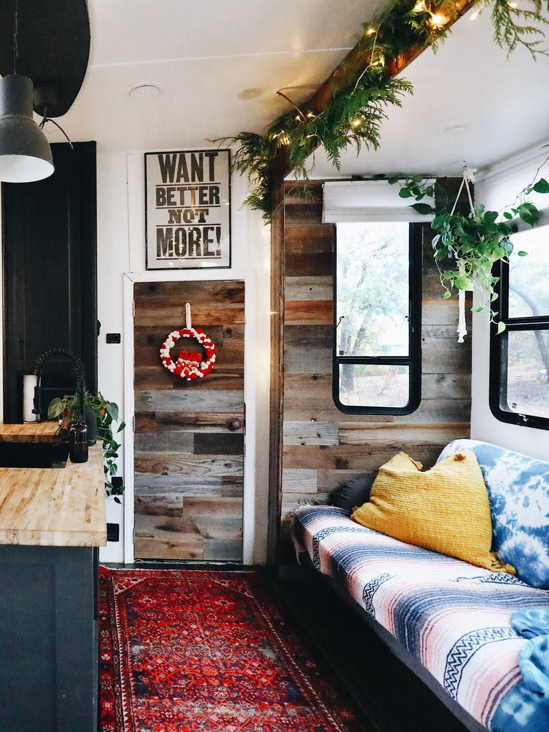 An RV kitchen decorated with pine boughs and lights for Christmas.