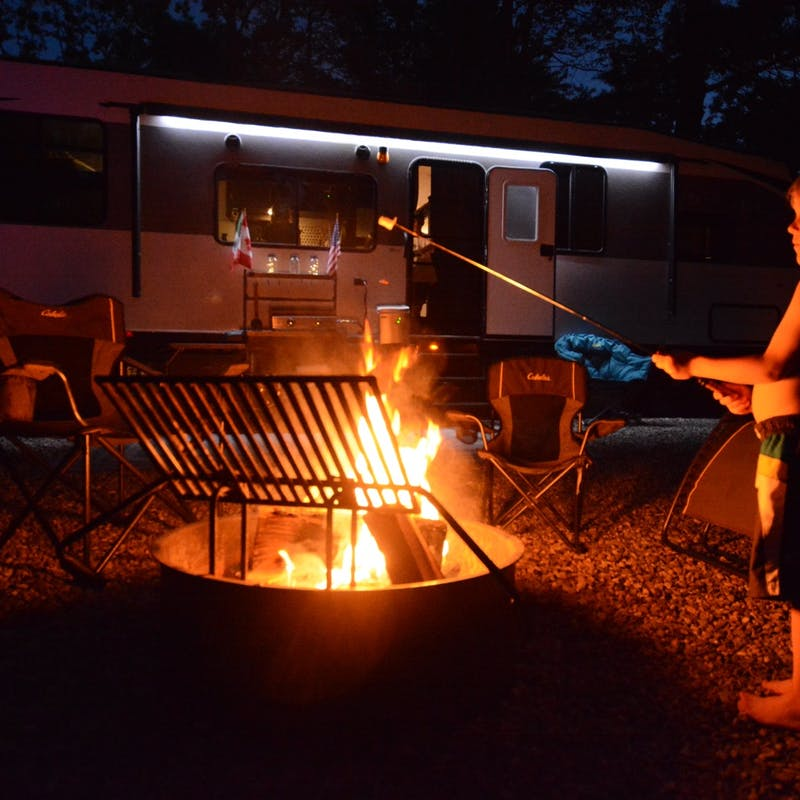A little boy roasting a marshmallow over a campfire.