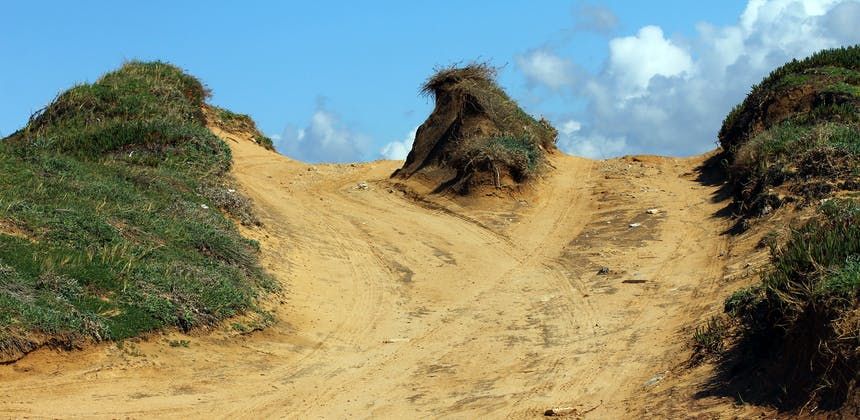 Sand trails converge over a hilltop.