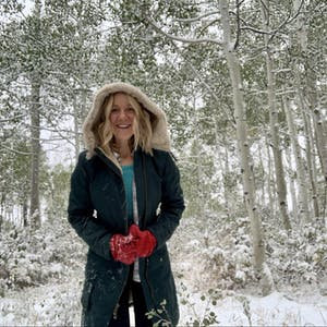 A woman smiles in the snow.