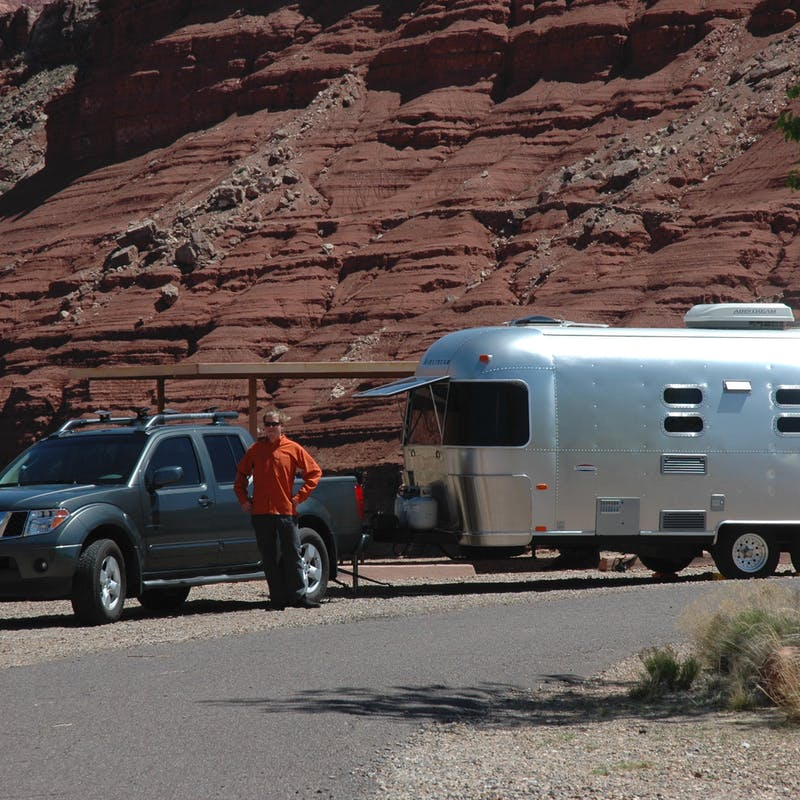 James posed with his truck and Airstream next to some red rock cliffs.
