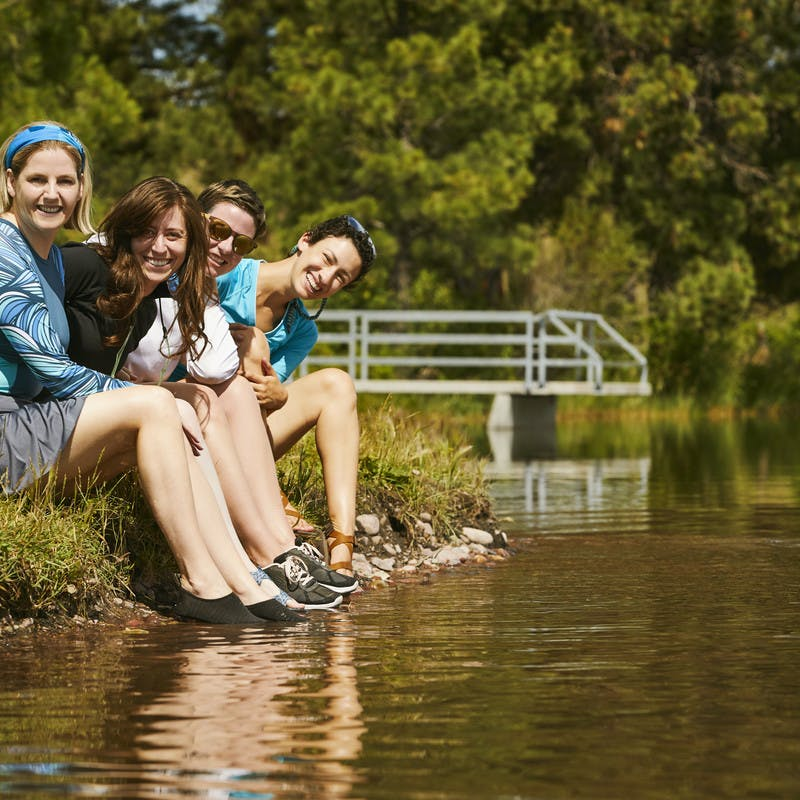 A group of participants rest their feet in the water of the Blackfoot River.
