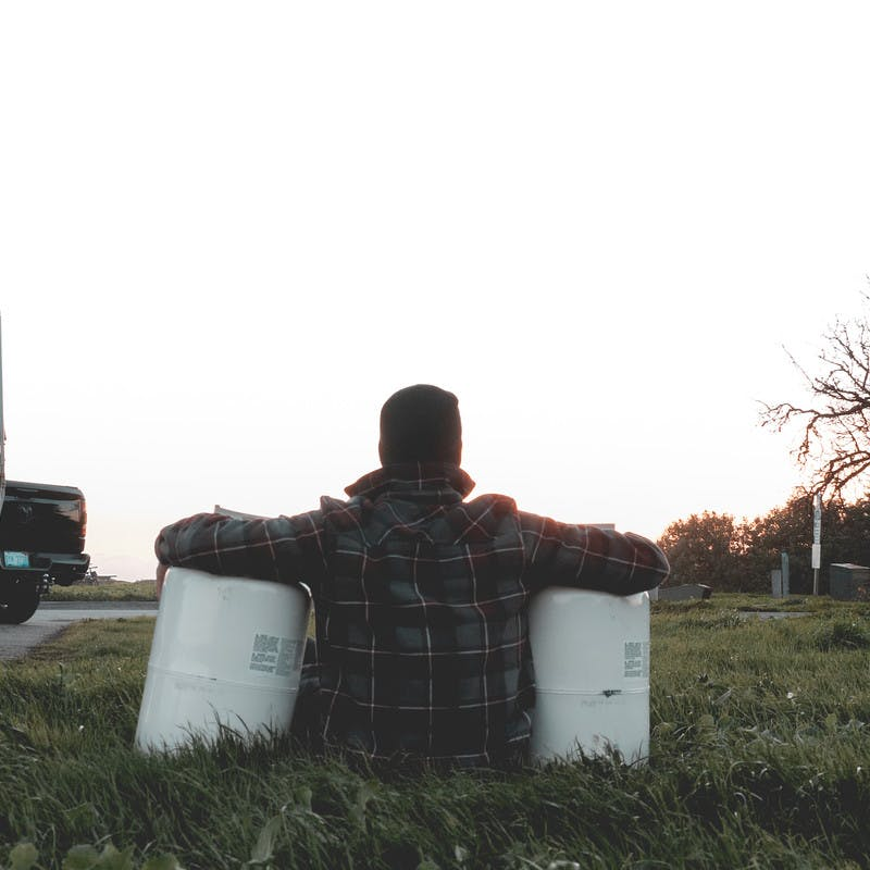 A man sitting in the grass with his arms looped around propane tanks on either side of his body.