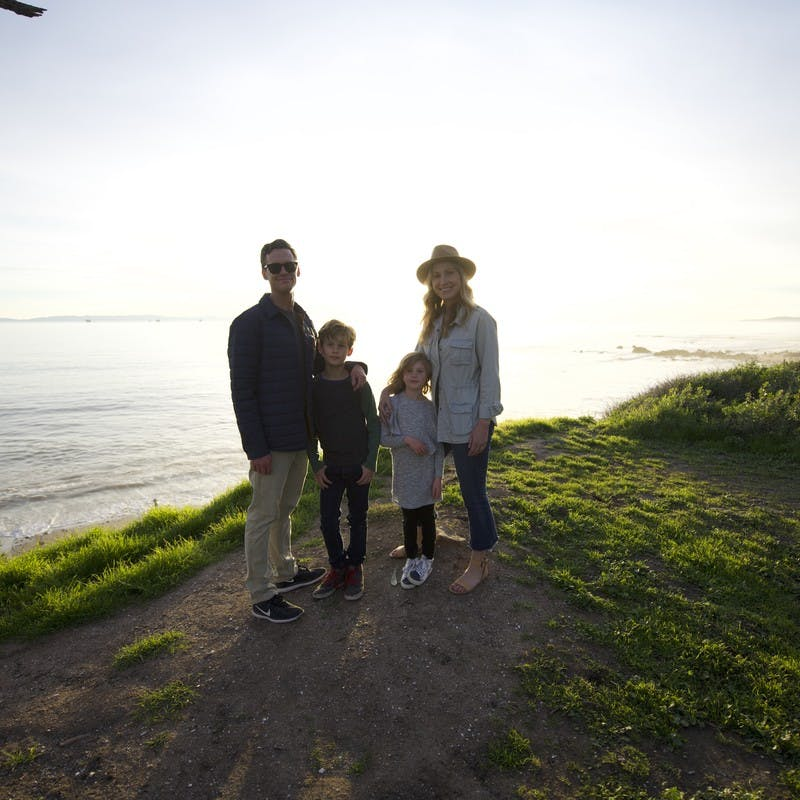 Family portrait of Sarah Schulz and her family on a clifftop, in front of the ocean during sunset.
