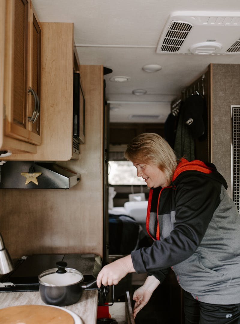 Kathy cooking inside her RV kitchen.