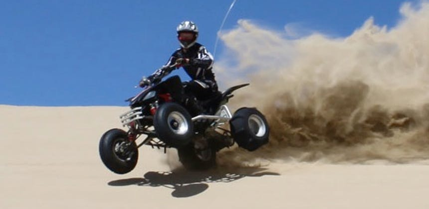 A quad bike rider throwing up sand at Oceano Dunes.