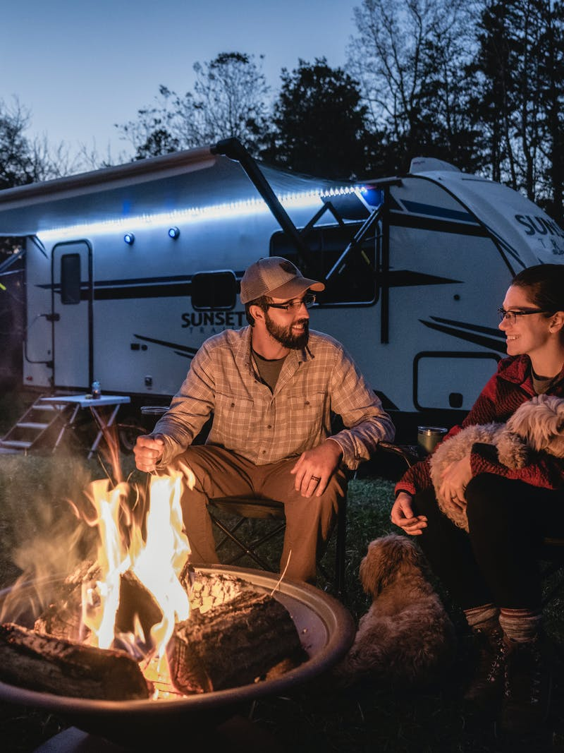 Todd and Marcia Schabel sit with their dogs by a fire pit at night in front of their Sunset Trail RV.