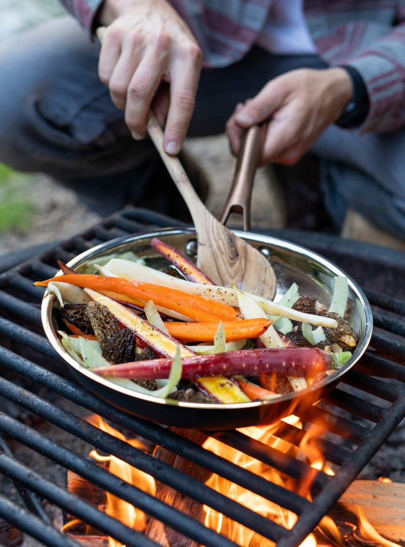Man in flannel stirs pan with wooden spoon, carrots, morels and fennel cooking over open campfire.