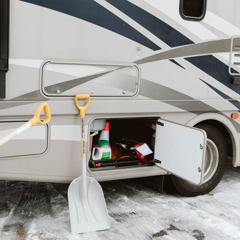 Storing snow shovels in an exterior RV cubby.